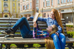 Μικρές όμορφες μαθήτριες που διαβάζουν ένα βιβλίο και που κάθονται στον πάγκο υπαίθριο Στοκ Εικόνες