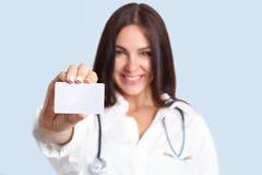 Μικρή άσπρη κενή κάρτα με το διαστημικό διαθέσιμο χέρι ` s αντιγράφων της όμορφης νοσοκόμας Καλός επαγγελματικός εύθυμος θηλυκός  Στοκ φωτογραφία με δικαίωμα ελεύθερης χρήσης