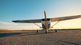 Μικρή έννοια αεροπορίας Το άσπρο και μπλε αεροπλάνο σε έναν διάδρομο, κλείνει επάνω φιλμ μικρού μήκους