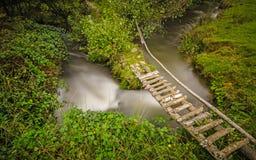 Μικρή αγροτική γέφυρα για πεζούς που διασχίζει έναν στριμμένο κολπίσκο Στοκ εικόνες με δικαίωμα ελεύθερης χρήσης