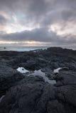 Μικρή λακκούβα στους απότομους βράχους Reykjanes που απεικονίζει το ηλιοβασίλεμα Στοκ Εικόνες