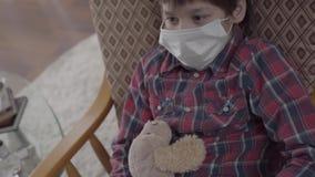 Μικρή ανεπαρκής συνεδρίαση αγοριών πορτρέτου στην πολυθρόνα με μια ιατρική μάσκα στο πρόσωπό του που κρατά το παιχνίδι στο σπίτι  φιλμ μικρού μήκους