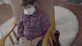Μικρή ανεπαρκής συνεδρίαση αγοριών πορτρέτου στην πολυθρόνα με μια ιατρική μάσκα στο πρόσωπό του που κρατά το παιχνίδι στο σπίτι  απόθεμα βίντεο