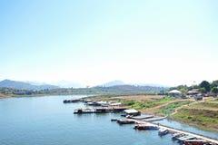 Μικρή αποβάθρα και πολλά σκάφη στον ποταμό με τα βουνά και το φως Στοκ Εικόνες