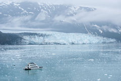 Μικρή βάρκα με τους τουρίστες που προσέχουν τον παγετώνα Hubbard. Αλάσκα Στοκ Φωτογραφία