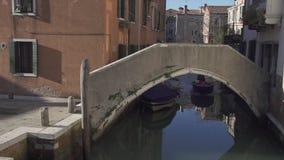 Μικρή βάρκα που περνά κάτω από μια γέφυρα σε ένα κανάλι στη Βενετία φιλμ μικρού μήκους