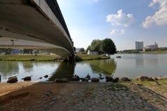 Μικρή για τους πεζούς συγκεκριμένη γέφυρα πέρα από έναν στενό ποταμό πόλεων Στοκ Εικόνες