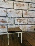 Μικρή διακόσμηση καρεκλών κινηματογραφήσεων σε πρώτο πλάνο στον ξύλινο πίνακα με τον άσπρο χρωματισμένο τοίχο τούβλου grunge Στοκ Εικόνες