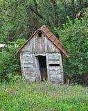 Μικρή εγκαταλειμμένη ξύλινη καμπίνα που περιβάλλεται από τα δέντρα Στοκ Εικόνες