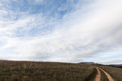 Μικρή εθνική οδός κάτω από το μεγάλο μπλε ουρανό και τα άσπρα σύννεφα Στοκ Εικόνες