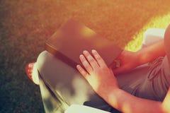 Μικρή εικόνα σπιτιών modelclose επάνω του ξύλινου πίνακα βιβλίων ανάγνωσης γυναικών outdooover υπαίθρια στον κήπο Φιλτραρισμένη ε Στοκ φωτογραφία με δικαίωμα ελεύθερης χρήσης