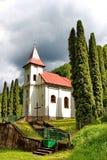 Μικρή εκκλησία που περιβάλλεται του χωριού από τα δέντρα με το cloudscape στο υπόβαθρο Στοκ εικόνα με δικαίωμα ελεύθερης χρήσης