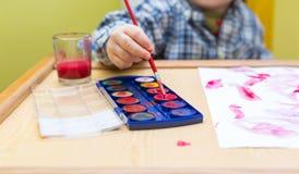 Μικρή ζωγραφική παιδιών με τα watercolors Στοκ Φωτογραφίες