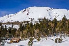 Μικρή καμπίνα στη βάση του χιονισμένου βουνού στοκ εικόνες