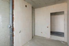 Μικρή κουζίνα στο νέο κτήριο, τους γυμνούς συγκεκριμένους και επικονιασμένους τοίχους, επικοινωνίες Στοκ φωτογραφία με δικαίωμα ελεύθερης χρήσης