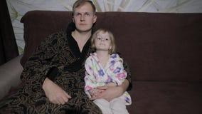 Μικρή κόρη με τον πατέρα της που προσέχει την ενδιαφέρουσα ταινία με τις μεγάλες συγκινήσεις απόθεμα βίντεο