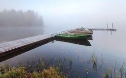 Μικρή ξύλινη αποβάθρα με τις βάρκες στην ακτή λιμνών Στοκ εικόνα με δικαίωμα ελεύθερης χρήσης