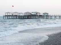 Μικρή ξύλινη αποβάθρα στην παραλία βοτσάλων και νερό aquamarine σε Turke Στοκ Φωτογραφία