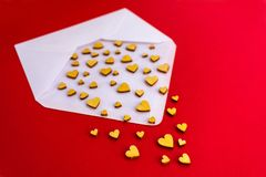 Μικρή ξύλινη μύγα καρδιών από έναν άσπρο φάκελο σε ένα κόκκινο υπόβαθρο o r στοκ φωτογραφίες με δικαίωμα ελεύθερης χρήσης