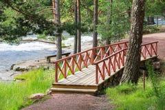 Μικρή ξύλινη γέφυρα με τα κόκκινα κιγκλιδώματα πέρα από το ρεύμα Στοκ εικόνα με δικαίωμα ελεύθερης χρήσης
