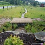 Μικρή ξύλινη γέφυρα με τον κολπίσκο κατωτέρω σε ένα αγρόκτημα Στοκ Φωτογραφίες