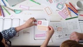 Μικρή ομάδα των σχεδιαστών UX που δημιουργούν το κινητό app σχεδιάγραμμα απόθεμα βίντεο