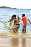 Μικρή ομάδα ψαράδων με τα καθαρά προσπάθεια πιασμένα ψάρια