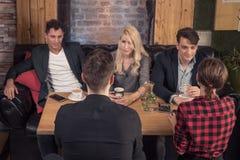 Μικρή ομάδα ανθρώπων που μιλά, καναπές καθίσματος, πίνακας Ι καφετεριών Στοκ φωτογραφία με δικαίωμα ελεύθερης χρήσης