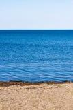 Μικρή παραλία στο μπλε νερό στον άσπρο ουρανό Στοκ Εικόνα