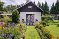 Μικρή παραδοσιακή καμπίνα εξοχικών σπιτιών με το κρεβάτι κήπων λουλουδιών Στοκ φωτογραφίες με δικαίωμα ελεύθερης χρήσης