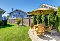 Μικρή περιοχή Patio με το ξύλινο επιτραπέζιες σύνολο και την ομπρέλα Στοκ φωτογραφία με δικαίωμα ελεύθερης χρήσης