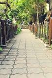 Μικρή πορεία στον κήπο, πεζοδρόμιο τούβλου με τον ξύλινο φράκτη Στοκ φωτογραφία με δικαίωμα ελεύθερης χρήσης