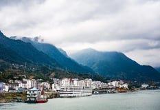 Μικρή πόλη στην άκρη ποταμών ` s Yangtze με το υπόβαθρο βουνών και σύννεφων Στοκ εικόνα με δικαίωμα ελεύθερης χρήσης