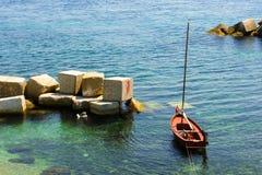 Μικρή πλέοντας βάρκα που δένεται κοντά στην ακτή Στοκ Εικόνες
