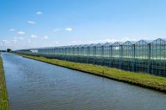 Μικραίνοντας άποψη προοπτικής ενός θερμοκηπίου κατά μήκος ενός καναλιού, δύση στοκ φωτογραφία με δικαίωμα ελεύθερης χρήσης