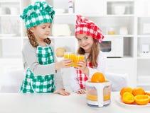 Μικροί αρχιμάγειρες που κατασκευάζουν το φρέσκο χυμό από πορτοκάλι Στοκ Φωτογραφίες