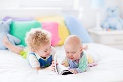 Μικροί αδελφοί που διαβάζουν ένα βιβλίο στο κρεβάτι Στοκ εικόνα με δικαίωμα ελεύθερης χρήσης