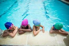 Μικροί κολυμβητές που μιλούν κλίνοντας στο poolside Στοκ Εικόνα