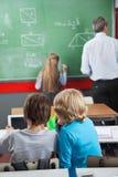 Μικροί μαθητές που χρησιμοποιούν την ψηφιακή ταμπλέτα στο γραφείο στοκ εικόνες