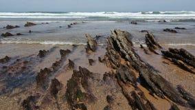 Μικροί σχηματισμοί βράχων στην αμμώδη παραλία απόθεμα βίντεο