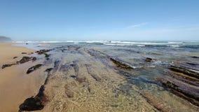 Μικροί σχηματισμοί βράχων στην αμμώδη παραλία φιλμ μικρού μήκους