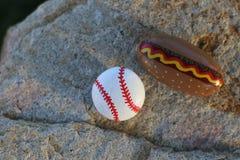 Μικροί χρωματισμένοι βράχοι μπέιζ-μπώλ και χοτ-ντογκ Στοκ Εικόνες