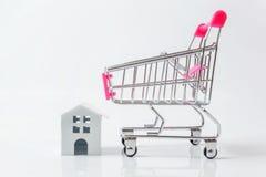 Μικροσκοπικά άσπρα σπίτι παιχνιδιών και κάρρο αγορών στο άσπρο υπόβαθρο στοκ φωτογραφία με δικαίωμα ελεύθερης χρήσης