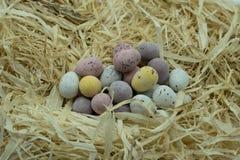 Μικροσκοπικά αυγά σοκολάτας σε έναν σωρό σε μια κλινοστρωμνή του αχύρου στοκ φωτογραφία