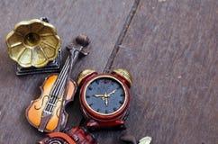 Μικροσκοπικά βιολί, ρολόγια και gramaphone στο ξύλινο πάτωμα Στοκ Φωτογραφίες