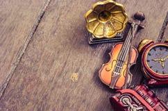 Μικροσκοπικά βιολί, ρολόγια, τραίνο και gramaphone στο ξύλινο πάτωμα Στοκ Εικόνα