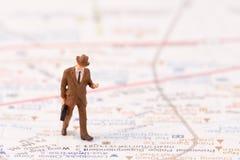 Μικροσκοπικά ειδώλια του ταξιδιώτη με το υπόβαθρο χαρτών Στοκ φωτογραφία με δικαίωμα ελεύθερης χρήσης