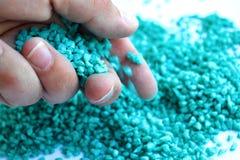 Μικροσκοπικά μπλε χαλίκια aqua που ανατρέπουν από ένα χέρι Στοκ φωτογραφίες με δικαίωμα ελεύθερης χρήσης