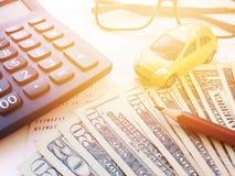 Μικροσκοπικά πρότυπο αυτοκινήτων, μολύβι, υπολογιστής, eyeglasses, χρήματα και βιβλιάριο ή οικονομική κατάσταση λογαριασμού ταμιε Στοκ Φωτογραφίες