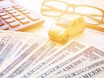 Μικροσκοπικά πρότυπο αυτοκινήτων, μολύβι, υπολογιστής, eyeglasses, χρήματα και βιβλιάριο ή οικονομική κατάσταση λογαριασμού ταμιε Στοκ φωτογραφίες με δικαίωμα ελεύθερης χρήσης